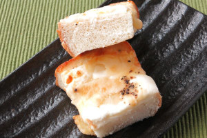 厚手のパンの上に、白いチーズフィリングが塗られています。