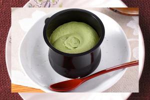黒みつソースを敷いた上にとろける抹茶わらび生地、抹茶ホイップをトッピングしたスプーンで食べるわらび餅。