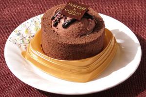 チョコ色のプレミアムロールケーキの上にドーム状のチョコムースとトッピングを盛った形。