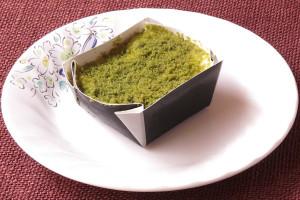 四角い紙容器に収まった抹茶色のケーキ。